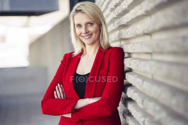 Blond lächelnde Geschäftsfrau mit verschränkten Armen im roten Anzug und Blick in die Kamera — Stockfoto
