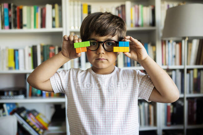 Portrait of serious little boy with glasses playing with building blocks at home — Stock Photo
