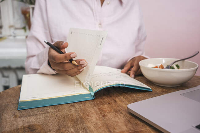 Close-up of young woman taking notes at table — Stock Photo