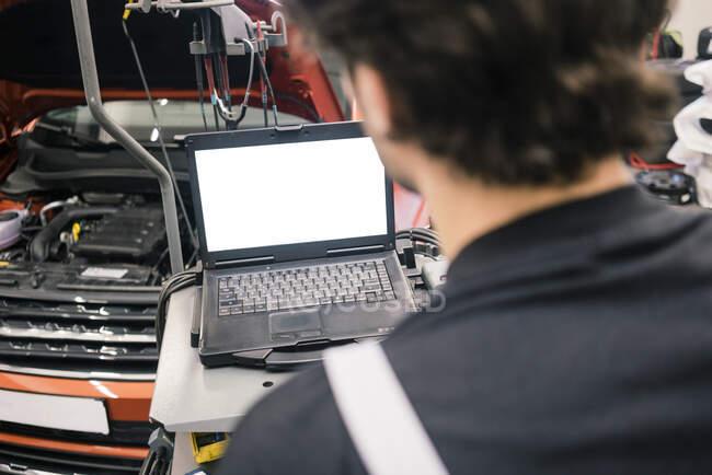 Автомобільний механік у майстерні за допомогою ноутбука. — стокове фото