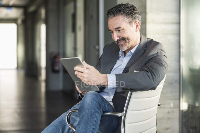 Mature businessman sitting on chair in office using tablet — Stock Photo