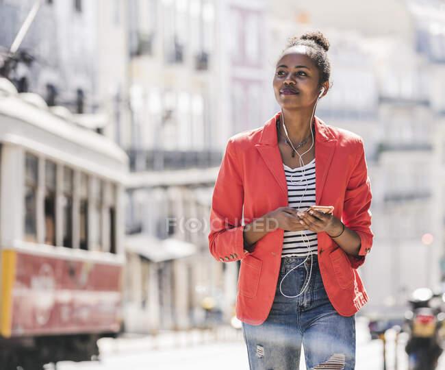 Giovane donna con auricolari e smartphone che si guarda intorno in città, Lisbona, Portogallo — Foto stock