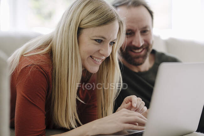 Couple sitting at home on couch, using laptop — Stock Photo