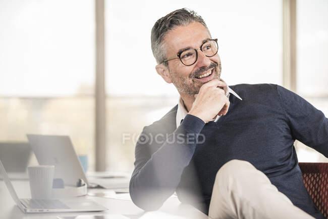 Lächelnder reifer Geschäftsmann sitzt am Schreibtisch im Büro — Stockfoto