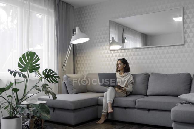 Жінка з ноутбуком сидить на дивані, дивлячись у вікно. — стокове фото