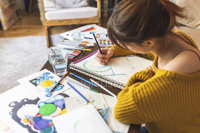Crop view of woman drawing with coloured pencil at home — Stock Photo