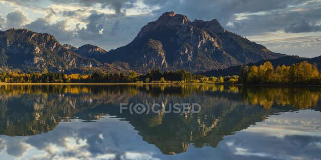 Німеччина, Баварія, Остальгу, гори відображені в озері з замком Нойшванштейн на відстані — стокове фото