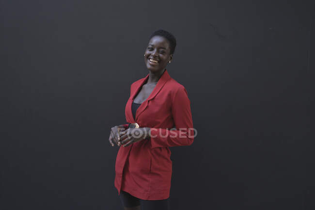 Young woman wearing red blazer in front of a grey wall — Stock Photo