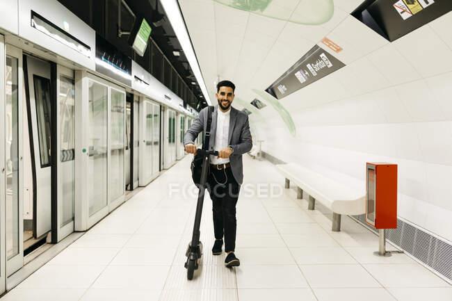 Jeune homme d'affaires avec scooter électrique dans la station de métro — Photo de stock