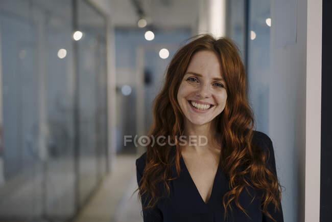 Ritratto di donna rossa felice sul pavimento dell'ufficio — Foto stock