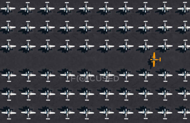 Aerial view of single orange colored airplane surrounded by exclusively white ones — Stock Photo