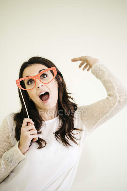 Portrait of playful young woman with comedy glasses — Stock Photo