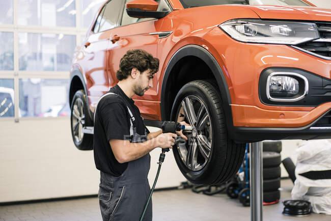 Автомобільний механік у майстерні змінює шину. — стокове фото