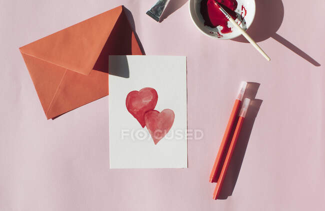Making a Valetine's day card, red envelope and card with hearts — Stock Photo