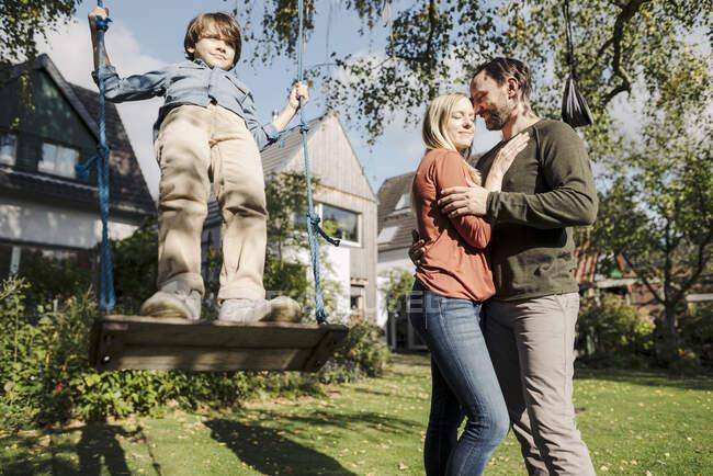Hijo balanceándose en el jardín con los padres besándose a su lado - foto de stock