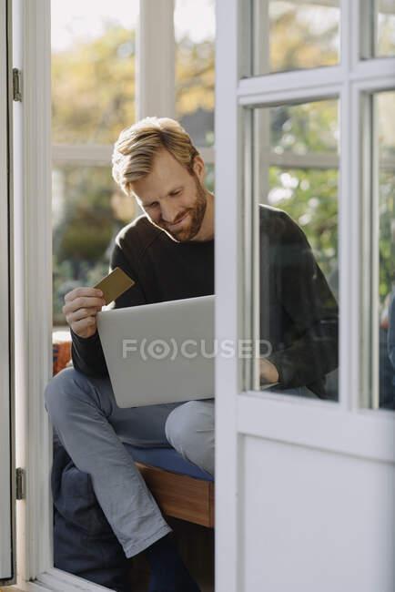 Sorrindo homem usando laptop e cartão de crédito em sunroom em casa — Fotografia de Stock