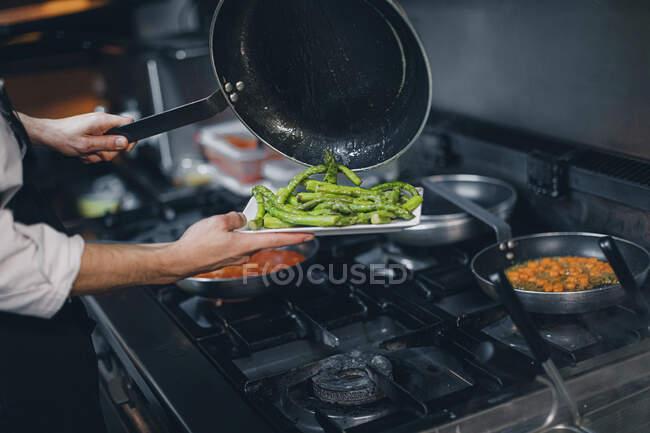 Chef preparing green asparagus dish in restaurant kitchen — Stock Photo