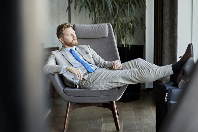 Businessman relaxing in hotel lobby — Stock Photo