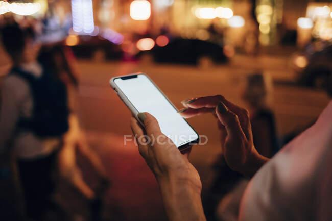 Руки жінок, що тримають смартфон вночі, зблизька. — стокове фото