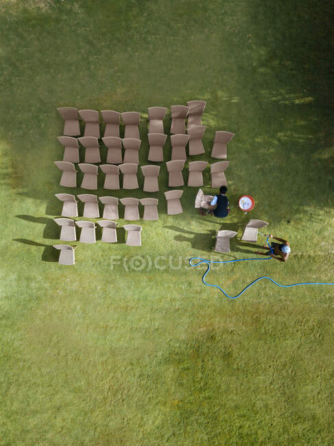 Indonesia, West Nusa Tenggara, Sumbawa, Aerial view of two young men washing chairs with garden hose — Stock Photo