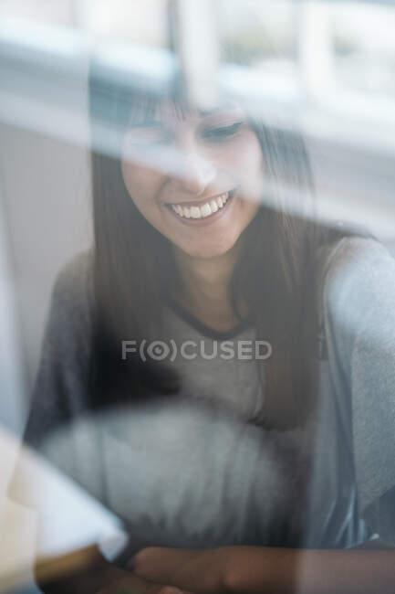 Retrato de una joven sonriente detrás del cristal de la ventana - foto de stock