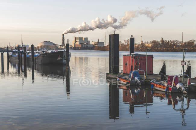 Allemagne, Hambourg, Bateaux amarrés sur la rive de l'Elbe avec centrale électrique de Moorburg en arrière-plan — Photo de stock