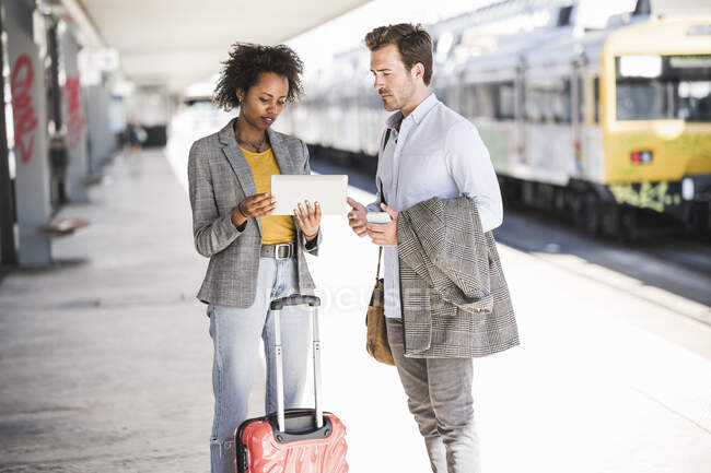 Young businessman and businesswoman using tablet together at the train station — Stock Photo
