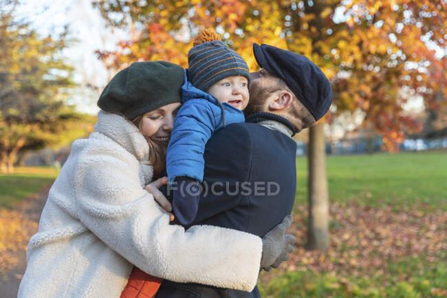 Felice coppia affettuosa con bambino al parco — Foto stock