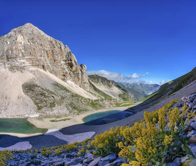 Италия, Умбрия, горный хребет Сибиллини, гора Вьоре, озеро Пилато и луна Пиццо-дель-Диаволо летом — стоковое фото