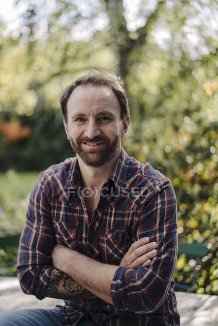 Retrato de homem maduro no jardim, com os braços cruzados — Fotografia de Stock