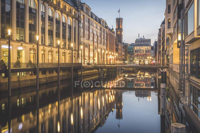 Germany, Hamburg, Street lights illuminating buildings along shiny Elbe river canal at dusk — Stock Photo