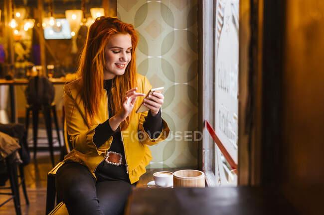 Retrato de una joven pelirroja feliz sentada en una cafetería usando un teléfono celular - foto de stock