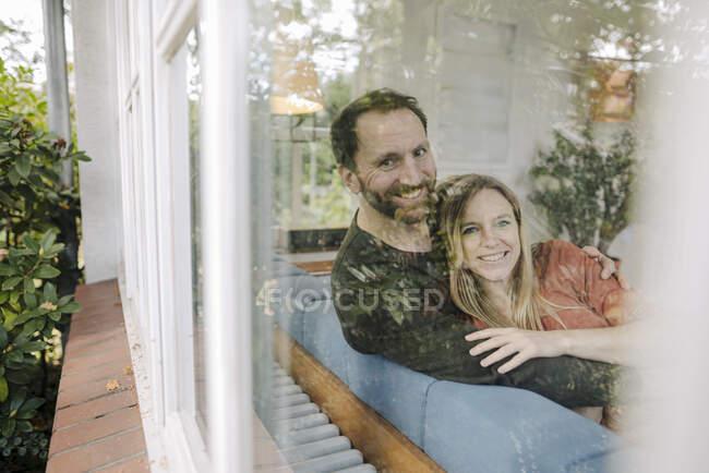 Pareja feliz sentada en el sofá, con arns alrededor, sonriendo - foto de stock