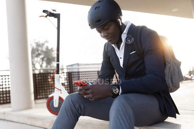 Молодий бізнесмен з штовхаючим скутером сидить на сходах під час заходу сонця за допомогою мобільного телефону та навушників. — стокове фото