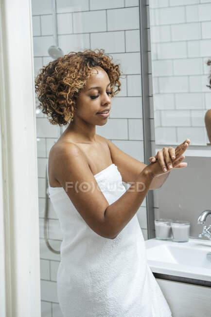 Mujer joven en el baño aplicando crema de manos - foto de stock