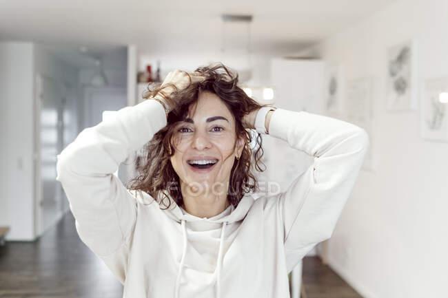 Porträt einer lachenden Frau mit den Händen im Haar zu Hause — Stockfoto