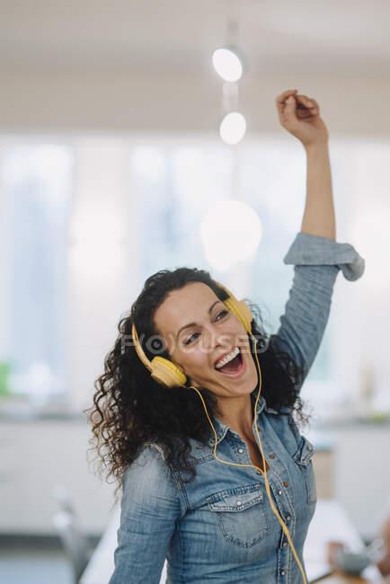 Mujer feliz escuchando música, cantando y bailando, usando teléfonos inteligentes y auriculares - foto de stock