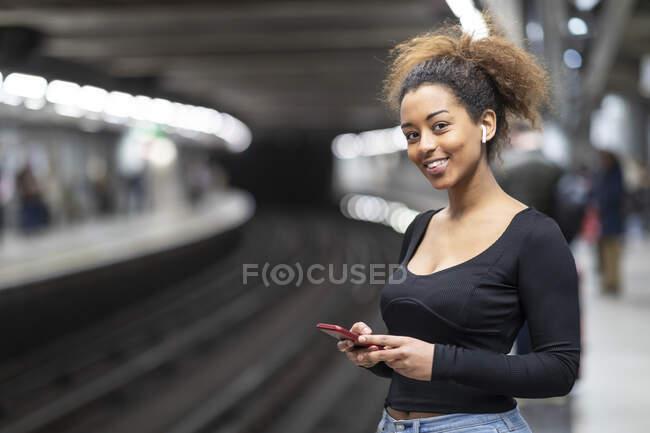 Retrato de jovem feliz com telefone celular e fones de ouvido na plataforma da estação de metrô — Fotografia de Stock