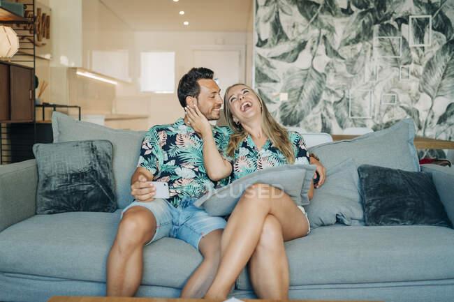 Счастливая пара сидит на диване в гостиной в гавайских рубашках — стоковое фото