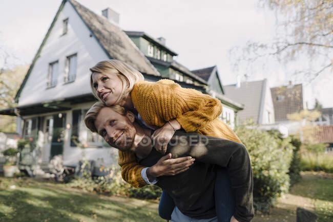 Мужчина катает жену на спине по саду — стоковое фото