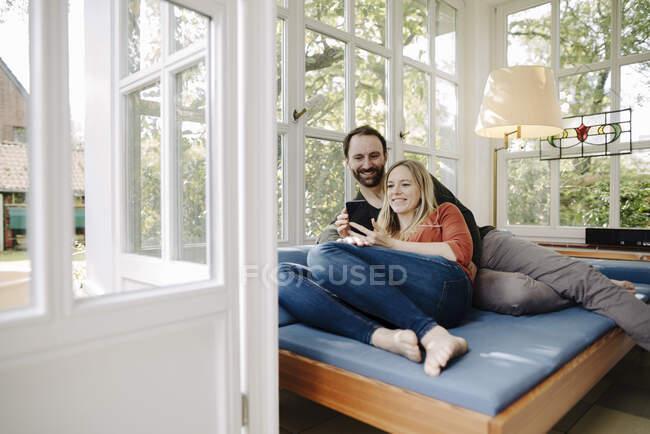 Щаслива пара відпочиває на дивані, користуючись смартфоном — стокове фото