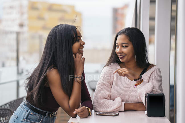 Two happy young women in rooftop cafe - foto de stock