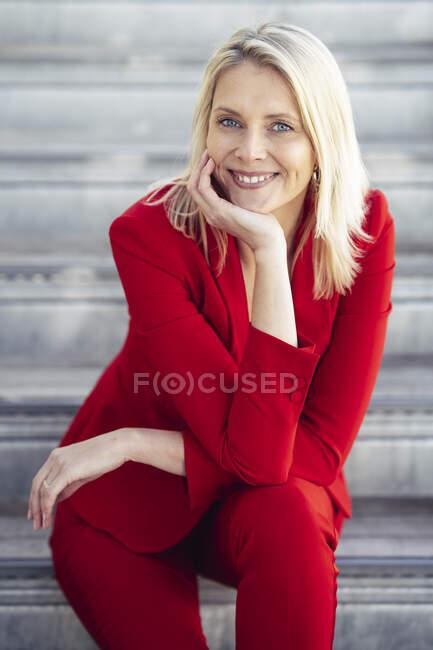 Blond lächelnde Geschäftsfrau im roten Anzug und mit Blick in die Kamera — Stockfoto