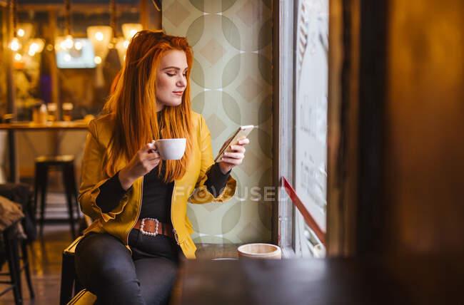 Rossa giovane donna seduta in un caffè con una tazza di caffè guardando il telefono cellulare — Foto stock