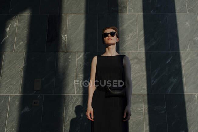 Червоноволоса жінка з сонцезахисними окулярами перед кам'яною стіною з тінями. — стокове фото