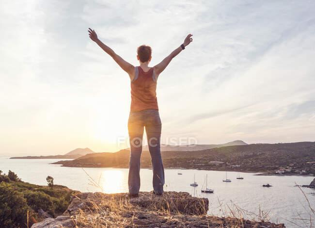 Жінка стоїть біля мису Саунтін з піднятими руками, задній вид, Аттіка, сірий — стокове фото