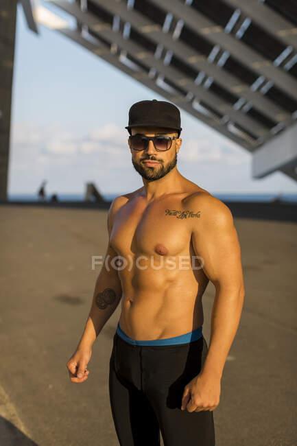 Hombre atlético con gorra de béisbol y gafas de sol - foto de stock