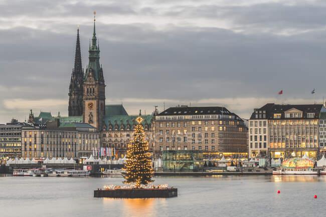Alemania, Hamburgo, Alstertanne iluminado al atardecer con Jungfernstieg paseo marítimo y la iglesia de San Nicolás en el fondo - foto de stock
