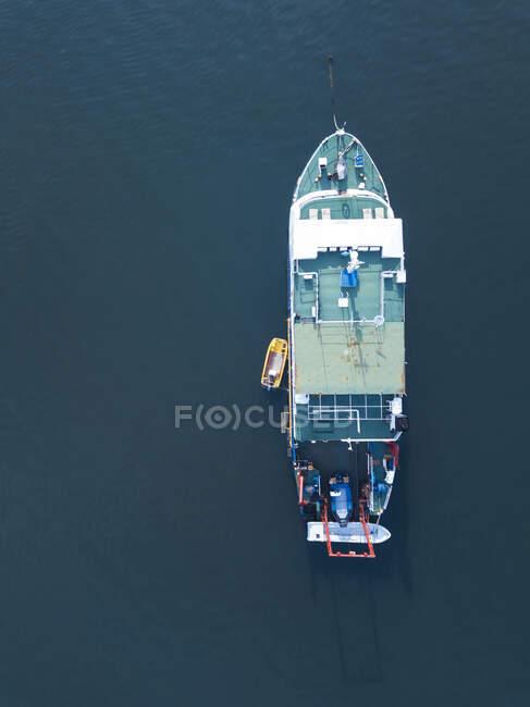 Индонезия, Бали, Серанган, Вид с воздуха на рыбацкую лодку, плавающую в голубой морской воде — стоковое фото