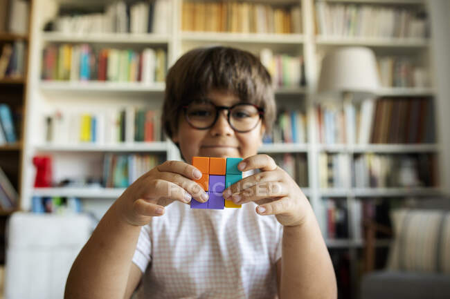 Smiling little boy holding cube made of building blocks — Stock Photo